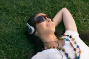 Young woman lying on grass, wearing headphones and sunglasses